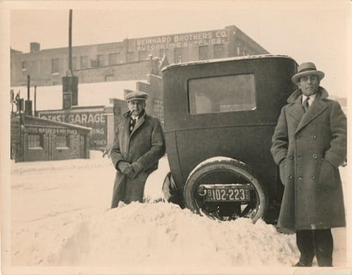 vintage men standing next to car in snow bank