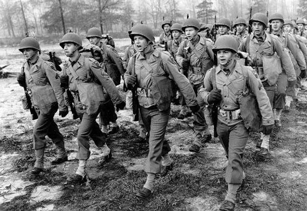 vintage military soldiers marching in formation through woods mud