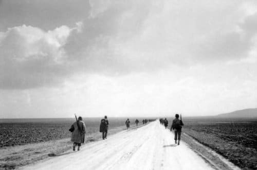 vintage soldiers marching along dirt road desolate landscape