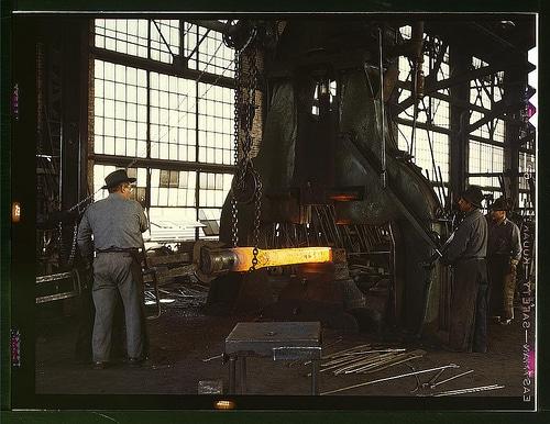 Vintage metal workers in workshop melting heating metal.