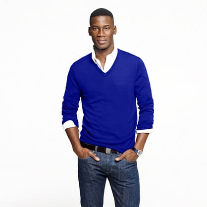 layering bright blue sweater over white button long sleeve shirt