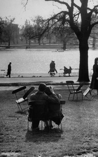 vintage couple hugging on park bench near lake somber