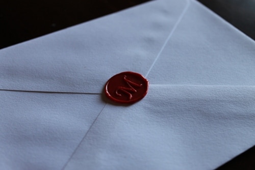 red wax seal on envelope with M monogram
