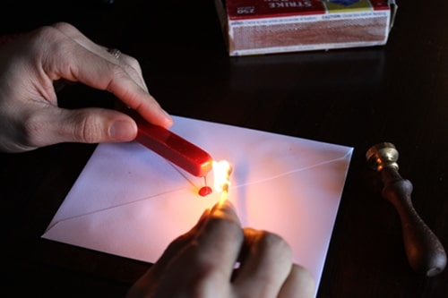 using match to melt wax for sealed envelope