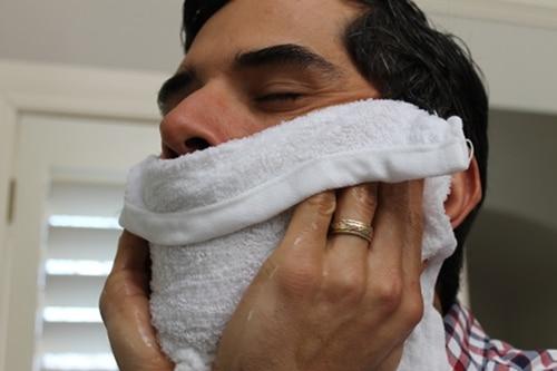 Homemade barbershop hot towel applying on face.