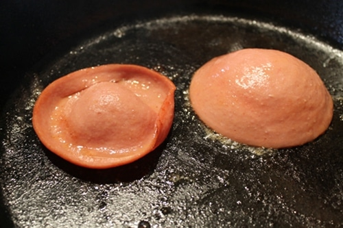 Bologna pieces frying on skillet.