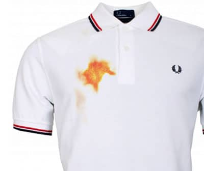 orange yellow mustard stain on white polo shirt