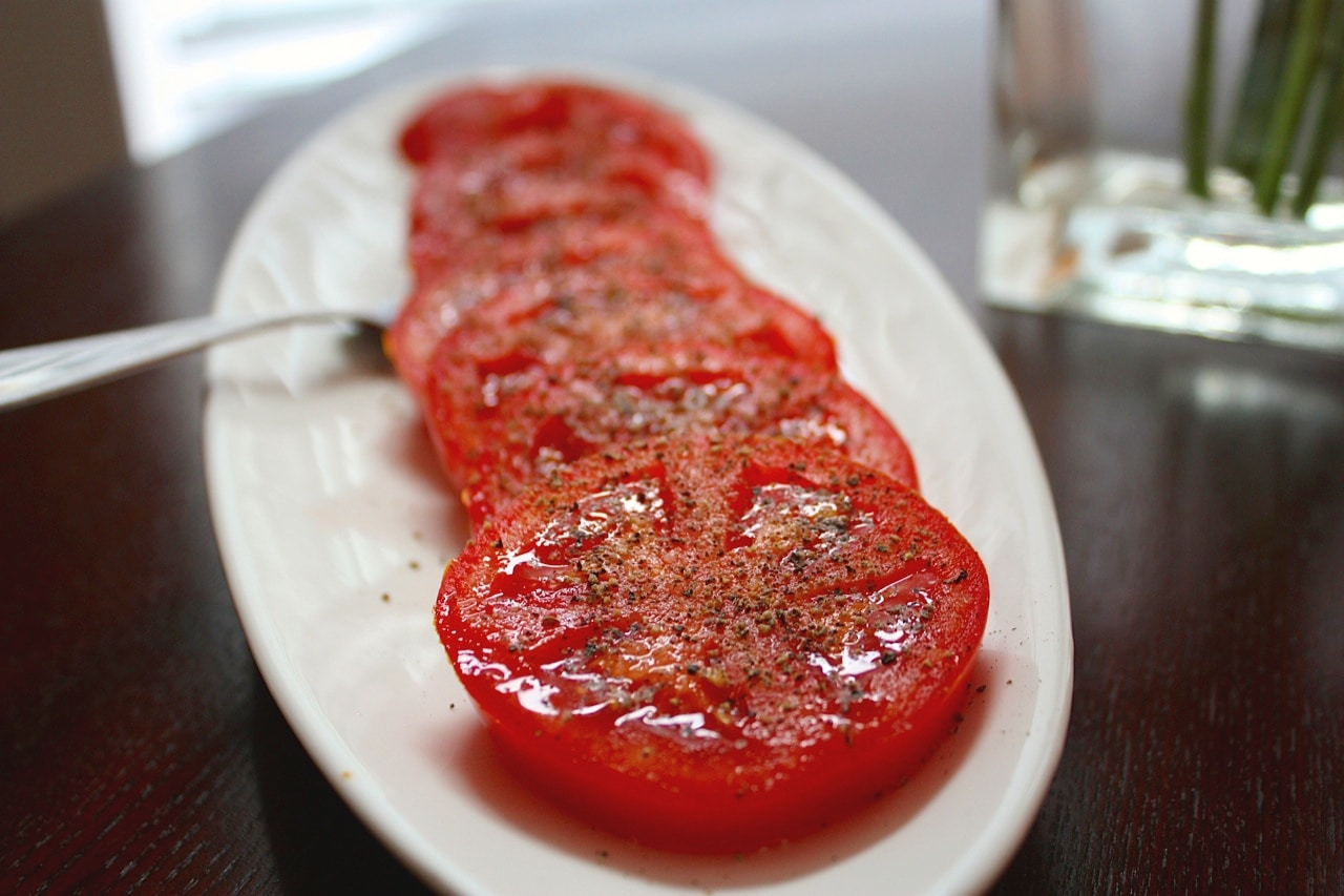 sliced fresh red tomatoes with pepper seasoning