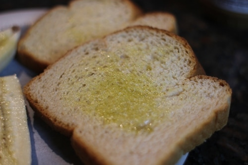 Vintage spread olive oil or butter on one side of each piece of bread.
