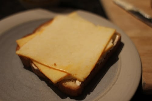 Vintage two slices of cheddar or muenster cheese over a plate.