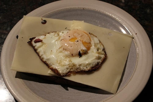 Vintage placed cheese and egg on piece of rye bread.