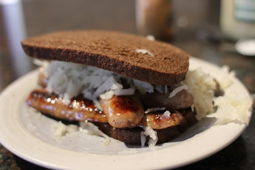 bratwurst sandwich with sauerkraut on pumpernickel bread