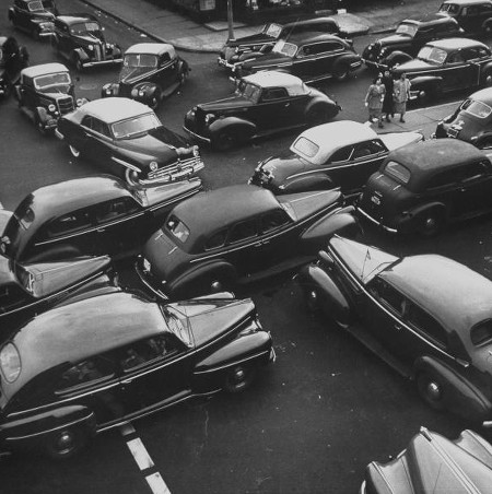 Vintage cards in gridlock at intersection mid 20th century.