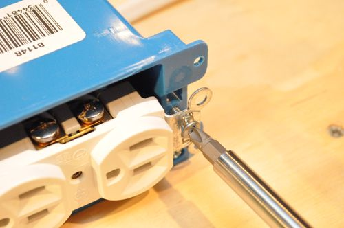 Carefully maneuver all the wires into the box and attach the receptacle with the two screws.