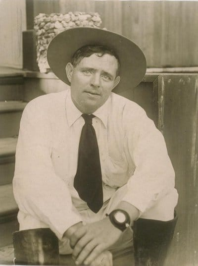 Vintage man in white shirt and wearing hat looking at front.