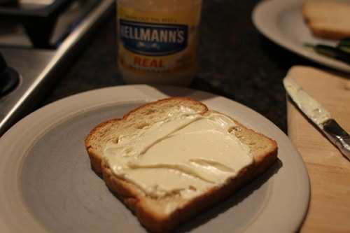 Vintage spreading a generous helping of mayo on white bread.