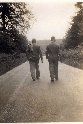 vintage men friends walking side by side down road