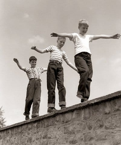 Vintage boys kids walking balancing along brick ball.