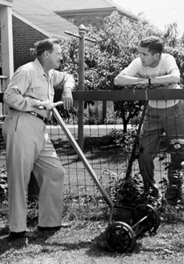 vintage neighbors talking over fence mowing lawns