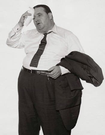 Vintage overweight man wiping brow with handkerchief.