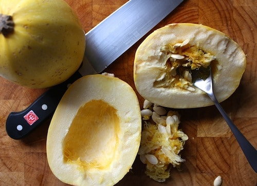 Spaghetti squash scooping seeds with spoon and knife.