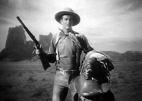 diligencia antigua película de cine occidental john wayne con rifle