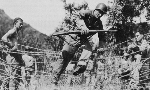 vintage soldier training jumping over barbed wire fence