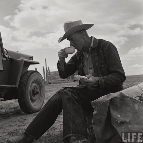 Vintage man cowboy rancher sitting down drinking coffee.