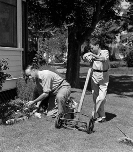 vintage boy mowing lawn with reel mower father doing gardening