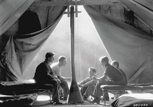 Vintage soldiers in opening of army tent talking.