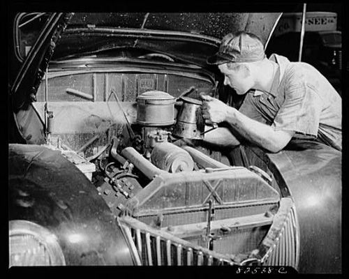 Vintage car auto mechanic working on engine under hood.