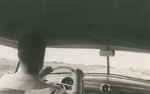 Vintage man driving down road interior of car.