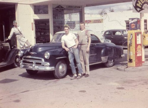 Vintage gas station men posing in front of car.