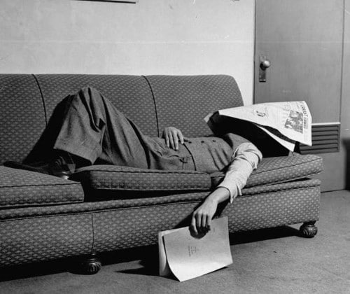 Vintage man napping sleeping on couch newspaper on head.