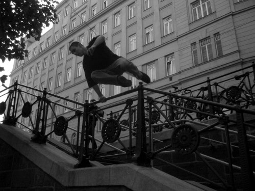 man jumping over stair rail black white photo parkour