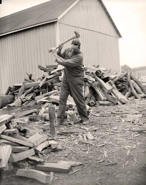 Vintage man splitting wood pile of logs around him.