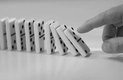 domino chain being pushed down with finger close up