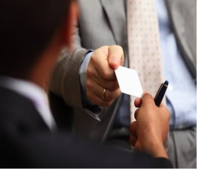 Man handing business card to another person close up.