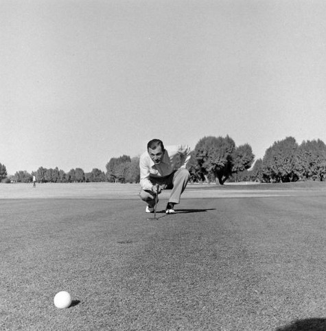 vintage golfer on green looking at hole bale foreground