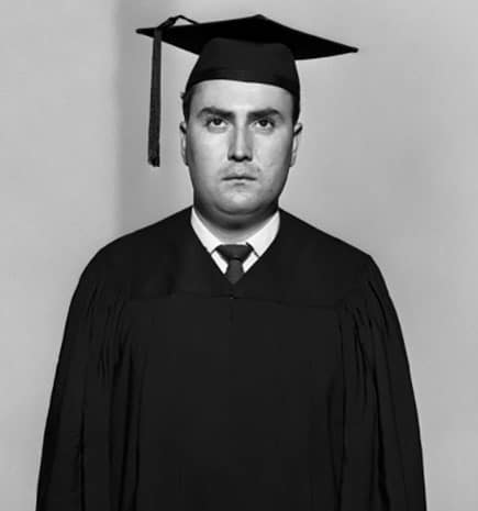 vintage man in graduation robe and hat looking despondent