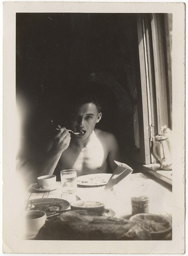 vintage young man eating fork in mouth at table