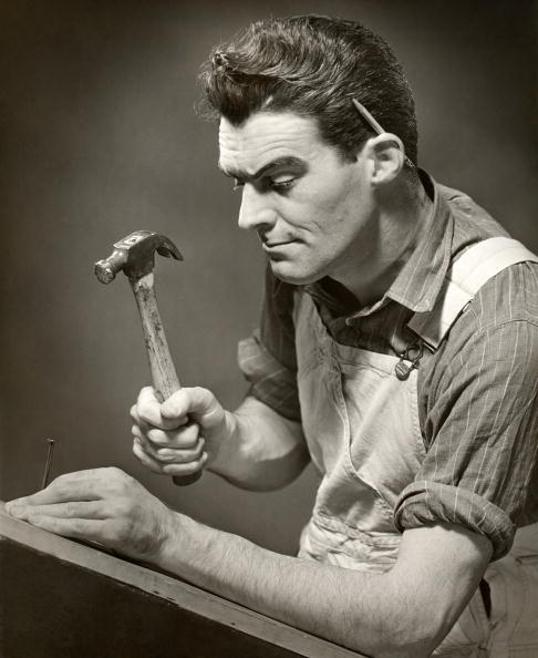 Vintage carpenter hammering a nail.