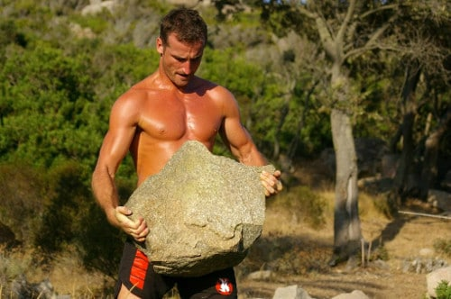 Man carrying large stone working out.
