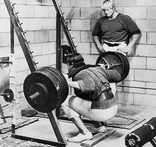 Vintage man deadlifting huge barbell in gym.