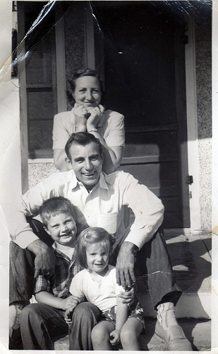 Vintage family with 2 kids sitting in front of house.
