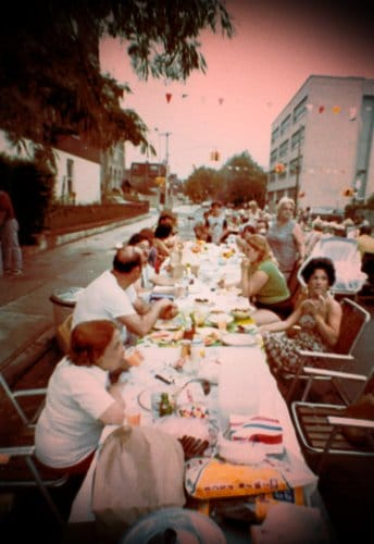 vintage block party people eating dinner talking long picnic tables