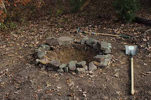 digging fire pit for backyard campfire rocks around edges rim