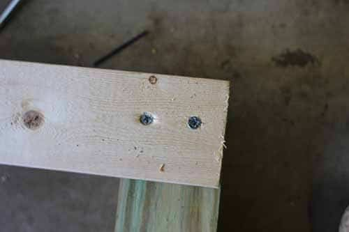 """Place one end of the 2x4 onto the glue on the end of the 4X4. Screw in two 3"""" wood screws."""