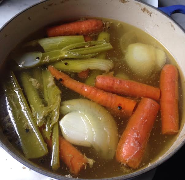 homemade diy Chicken Stock in large pot with celery carrots onions