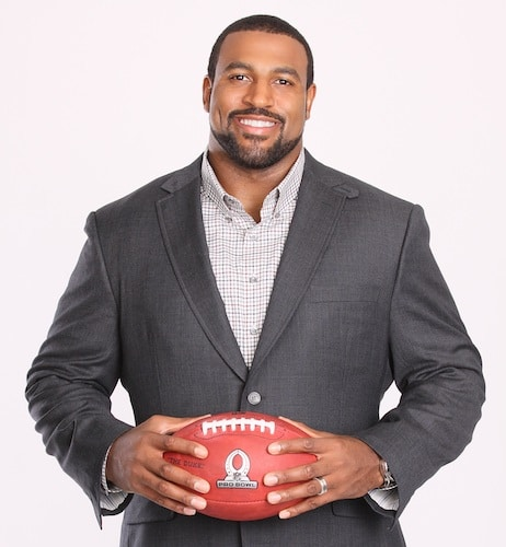 duane brown houston texans wearing suit holding football